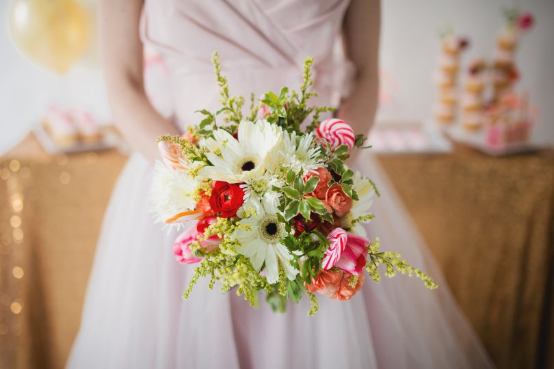 Bridal bouquet made with gerber daisies, ranunculus, tulips, solidago and lollipops | a bright pop of color for any winter wedding | designed by Natasha Price of alaskaknitnat.com | photo by Dolce Vita Photo Studio