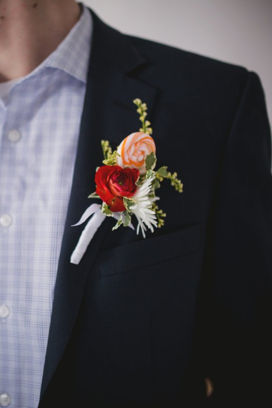 Boutonniere with ranunculus, snowflake mum, solidago and lollipop
