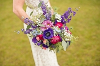 Bridal bouquet made with purple anemones, fuchsia ranunculus, blue nigella, purple larkspur, daisies, baby's breath, pink spray roses and seeded eucalyptus | designed by Natasha Price of Alaskaknitnat.com