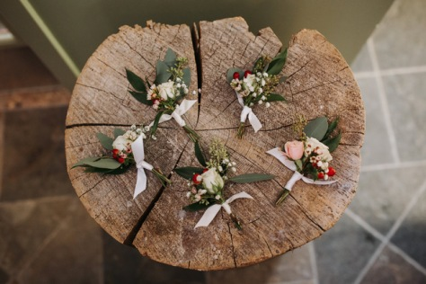 wintertime boutonniere's with blush, white and red | designed by Natasha Price and photo by Grace Adams Photography