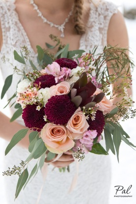Winter weddings: a bridal bouquet made with peach roses, burgundy chrysanthemums, carnations, alstroemeria, carnations and wax flower. Designed by Natasha Price of Alaskaknitnat.com