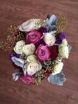 Alaska Winter Wedding   purple roses, plum mini carnations, burgundy carnations, white roses, dusty miller, eucalyptus and wax flower. Bound with white ribbon and a purple corset. Designed by Natasha Price of Alaskaknitnat.com