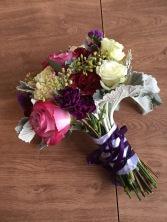 Alaska Winter Wedding | purple roses, plum mini carnations, burgundy carnations, white roses, dusty miller, eucalyptus and wax flower. Bound with white ribbon and a purple corset. Designed by Natasha Price of Alaskaknitnat.com