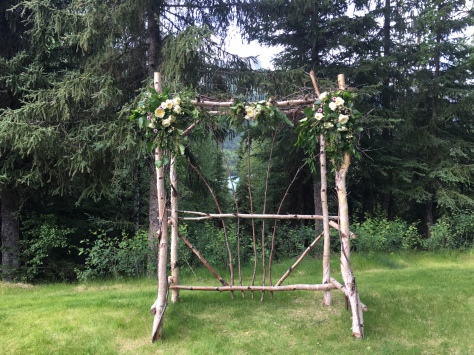 Floral wedding arch arrangements made with garden roses, button mums, hypericum, wax flower, eucalyptus and foraged Alaska greens. |Designed by Natasha Price of Alaskaknitnat.com