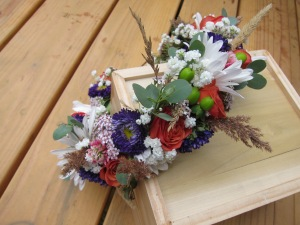 A bridal flower crown made with orange spray rose, purple Japanese aster, white daisies, green hypericum berry, gunnii eucalyptus, baby's breath and foraged yarrow, grass and clover.   Designed by Natasha Price of alaskaknitnat.com