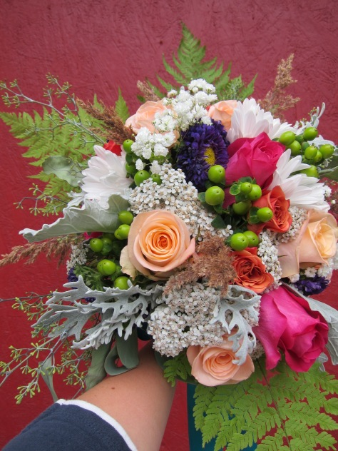 Alaska bridal bouquet with peach and fuchsia roses, purple Japanese aster, green hypericum berry, dusty miller, baby's breath, orange spray roses, seeded eucalyptus and foraged yarrow, grass and ferns. The perfect wild Alaska wedding bouquet. | Designed by Natasha Price of alaskaknitnat.com