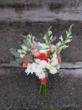A creamsicle wedding   bridal bouquet made with peach roses, football mums, snapdragon, spray roses, lisianthus, limonium, hypericum and seeded eucalyptus. Designed by Natasha Price of Alaskaknitnat.com