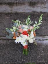 A creamsicle wedding | bridal bouquet made with peach roses, football mums, snapdragon, spray roses, lisianthus, limonium, hypericum and seeded eucalyptus. Designed by Natasha Price of Alaskaknitnat.com
