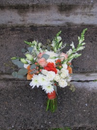 A creamsicle wedding | bridal bouquet made with peach roses, football mums, snapdragon, spray roses, lisianthus, limonium, hypericum and seeded eucalyptus. Designed by Natasha Price of Alaskaknitnat.com