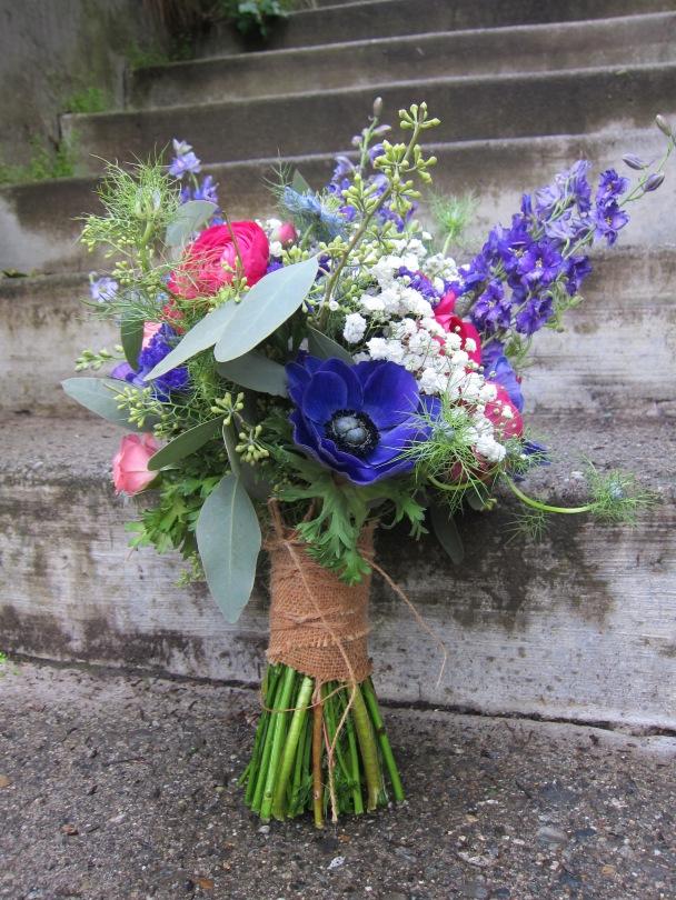 Bridal bouquet made with purple anemones, fuchsia ranunculus, blue nigella, purple larkspur, daisies, baby's breath, pink spray roses and seeded eucalyptus   designed by Natasha Price of Alaskaknitnat.com