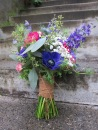 Bridal bouquet made with purple anemones, fuchsia ranunculus, blue nigella, purple larkspur, daisies, baby's breath, pink spray roses and seeded eucalyptus | designed by Natasha Price of Alaskaknitnat.com