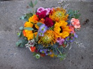 Alaska Weddings: a bridal bouquet made with sunflower, protea, mini carnation, button mums, mini asters, limonium and eucalyptus. Just perfect for a lakeside wedding. Designed by Natasha Price of Alaskaknitnat.com