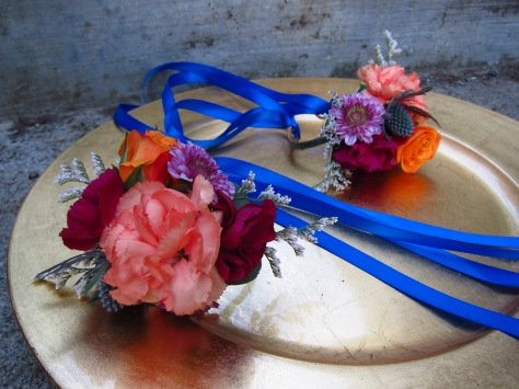 Wrist corsages made with peach mini carnations, orange spray roses, purple button mums and limonium | designed by Natasha Price of Alaskaknitnat.com