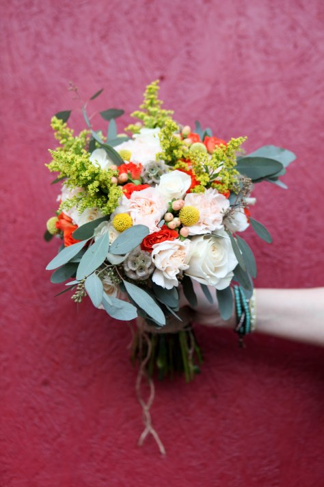 A perfect fall bridal bouquet. Solidago, white roses, orange spray roses, salmon hypericum berry, billy ball, scabiosa pods, peach carnation and seeded eucalyptus wrapped in burlap with jute twine corset | designed by Natasha Price of alaskaknitnat.com