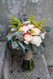 A perfect fall bridal bouquet. Solidago, white roses, orange spray roses, salmon hypericum berry, billy ball, scabiosa pods, peach carnation and seeded eucalyptus wrapped in burlap with jute twine corset   designed by Natasha Price of alaskaknitnat.com