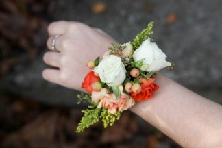 Autumn wrist corsage made with orange spray rose, billy ball, hypericum, solidago and seeded eucalyptus | designed by Natasha Price of alaskaknitnat.com