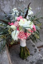 Shabby chic bridal bouquet made with eucalyptus, feathers, carnations, football mums, roses, stock and spray roses | designed by Natasha Price of Alaskaknitnat.com