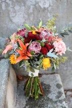 Rustic wedding bouquet made with protea, mini sunflowers, orange lilies, carnations, burgundy button mums, eucalyptus and limonium   designed by Natasha Price of Alaskaknitnat.com