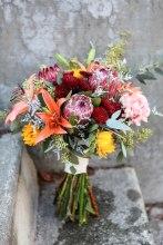 Rustic wedding bouquet made with protea, mini sunflowers, orange lilies, carnations, burgundy button mums, eucalyptus and limonium | designed by Natasha Price of Alaskaknitnat.com