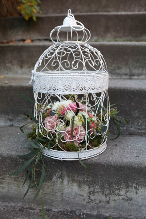 Birdcage flower arrangement for a fairy tale wedding. Made with eucalyptus, carnations, football mums, roses, stock and spray roses | designed by Natasha Price of Alaskaknitnat.com
