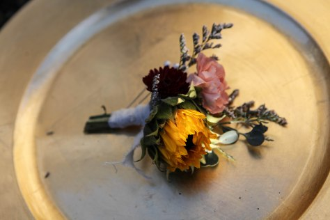 rustic fall wedding boutonniere made with mini carnation, burgundy button mum, mini sunflower, eucalyptus and limonium | Designed by Natasha Price of Alaskaknitnat.com