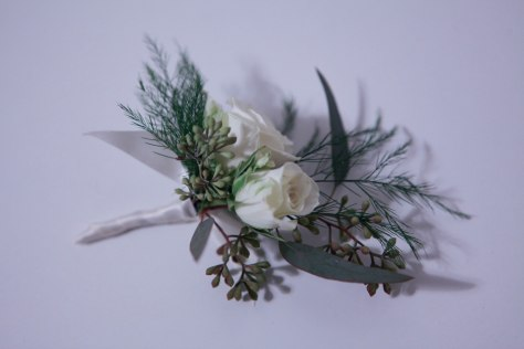 Boutonniere made with white spray rose, seeded eucalyptus and tree fern | designed by Natasha Price of alaskaknitnat.com